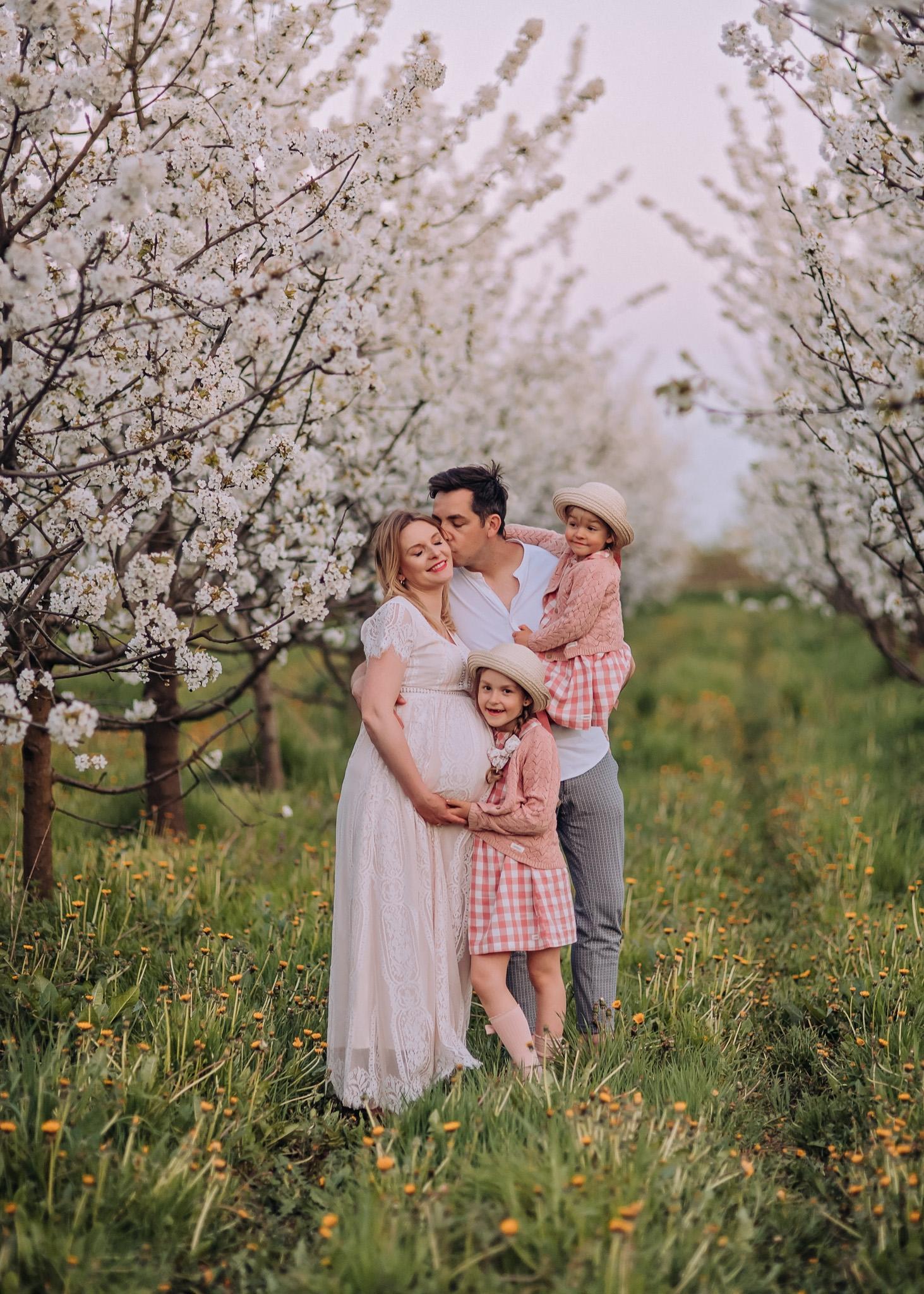 zdjęcia rodzinne w kwitnącym sadzie w plenerze wiosna